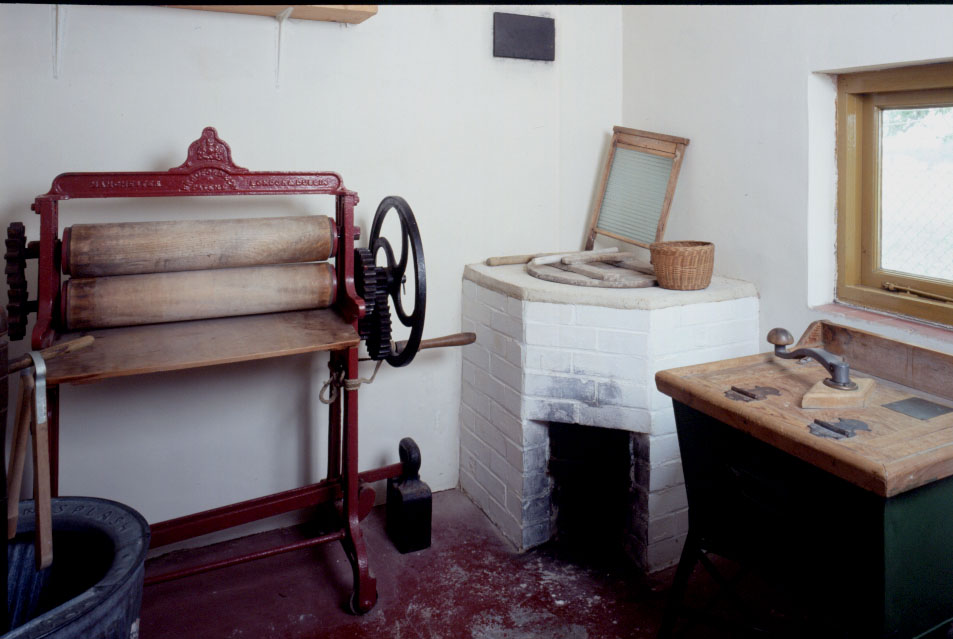 Items on display in the wash room of Walnut Tree Cottage, including a mangle, dolly and washing machine