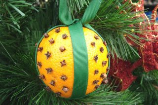 Image of an orange with cloves in, wrapped in green ribbon and hanging from a Christmas tree