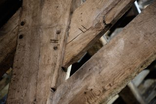 Detail of the stone barn roof showing the Roman numerals inscribed into the timbers